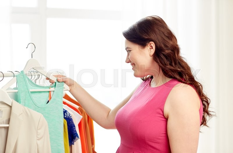 Stock image of 'clothing, fashion, style and people concept - happy plus size woman choosing clothes at home wardrobe'