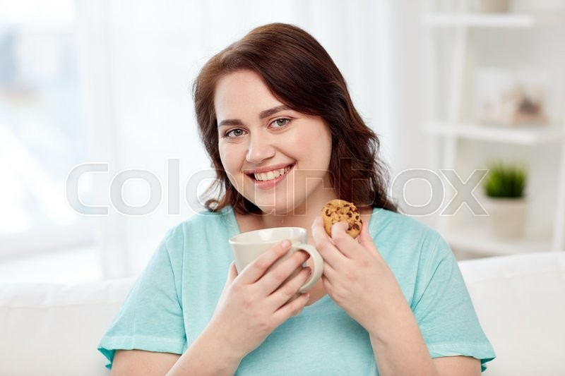 Stock image of 'people, junk food, unhealthy eating and leisure concept - happy plus size young woman with cup of tea with cookie at home'