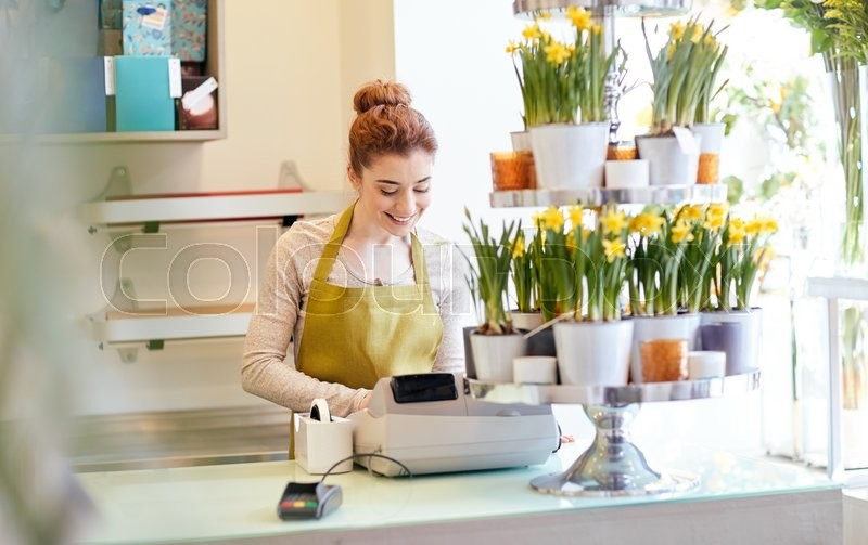 Stock image of 'people, business, sale and floristry and concept - happy smiling florist woman at flower shop cashbox on counter'