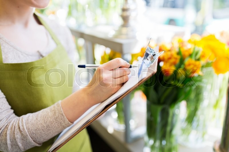 Stock image of 'people, sale, retail, business and floristry concept - close up of happy smiling florist woman with clipboard writing and making notes order at flower shop'