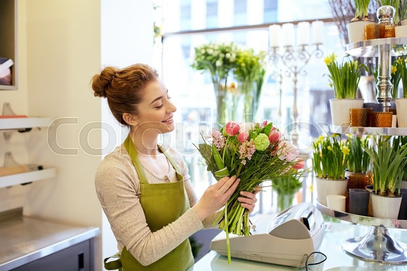 Stock image of 'people, business, sale and floristry concept - happy smiling florist woman making bunch at flower shop'