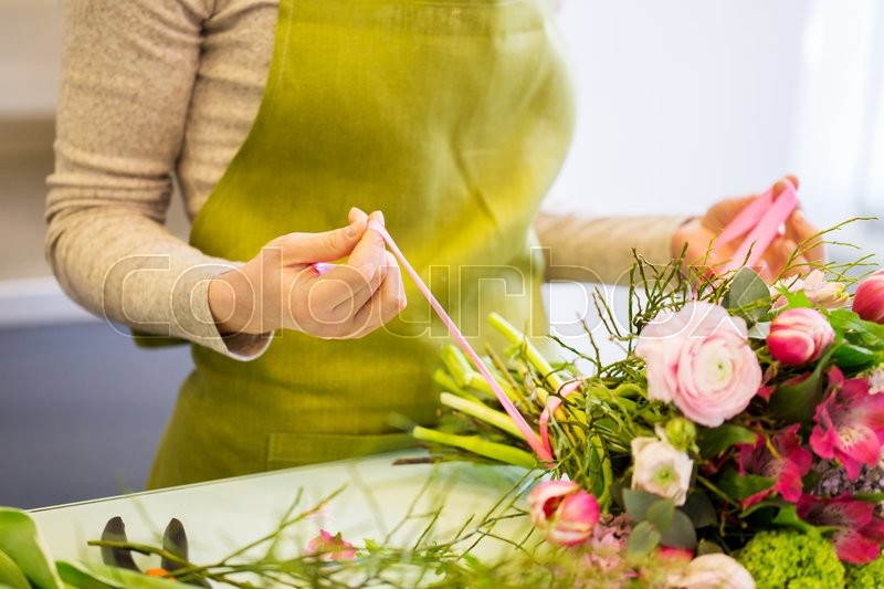 Stock image of 'people, business, sale and floristry concept - close up of florist woman making bunch at flower shop'