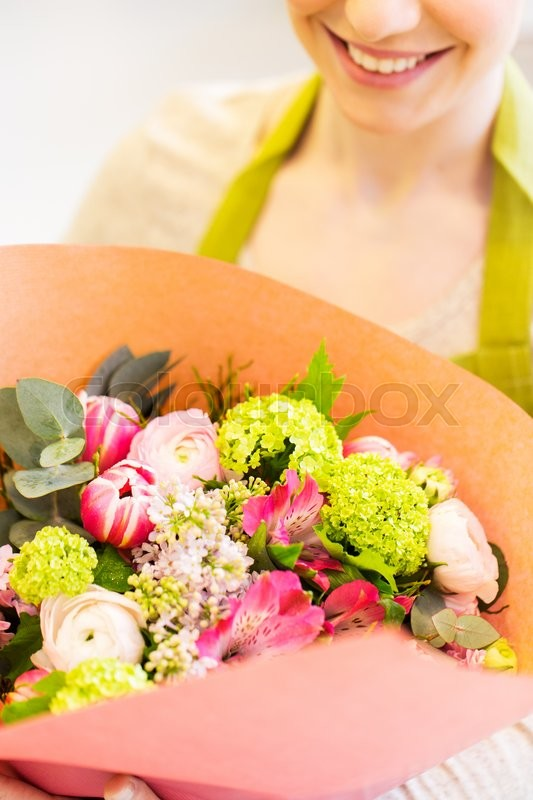 Stock image of 'people, business, sale and floristry concept - close up of happy smiling florist woman holding bunch of flowers wrapped into paper at flower shop'