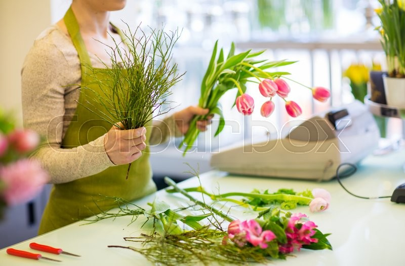 Stock image of 'people, business, sale and floristry concept - close up of florist woman making tulip bunch at flower shop'