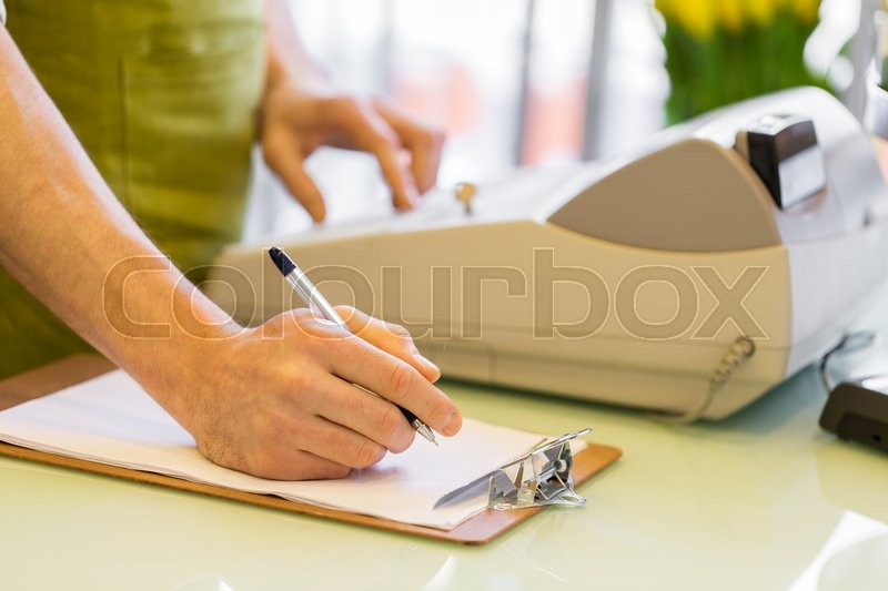 Stock image of 'people, sale, retail, business and floristry concept - happy smiling florist man with clipboard and cashbox writing and making notes at flower shop counter'