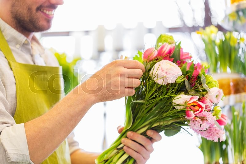 Stock image of 'people, business, sale and floristry concept - close up of happy smiling florist man making bunch at flower shop'