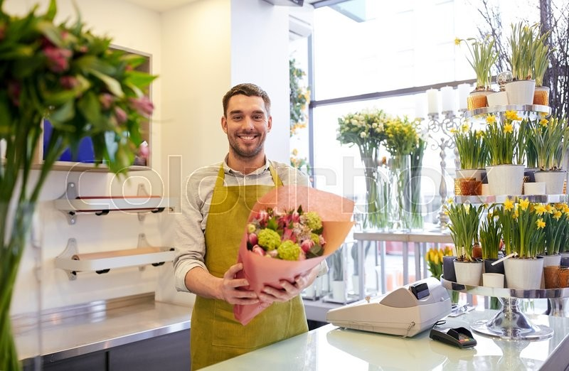 Stock image of 'people, business, sale and floristry concept - happy smiling florist man with bunch at flower shop'