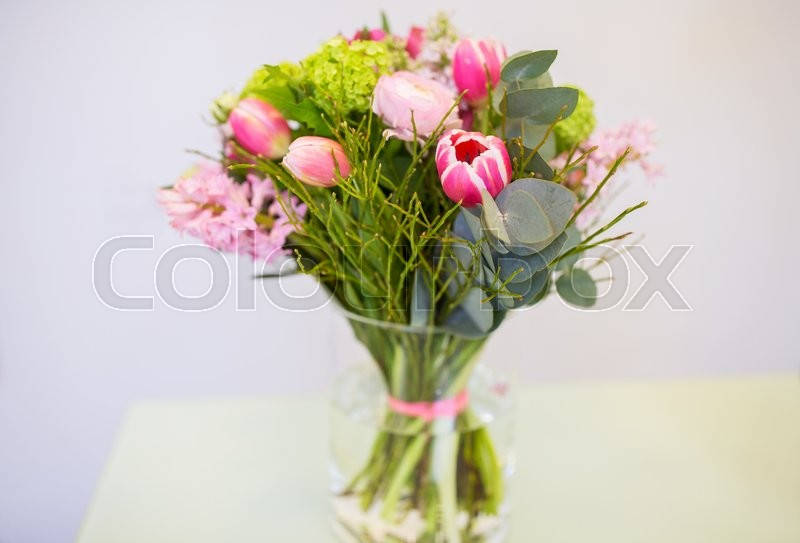 Stock image of 'gardening, floristry, holidays and flora concept - close up of bunch in vase at flower shop'