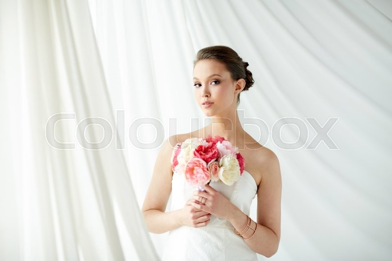 Stock image of 'beauty, jewelry, people and luxury concept - beautiful asian woman or bride in white dress with peony flower, golden ring and bracelet'