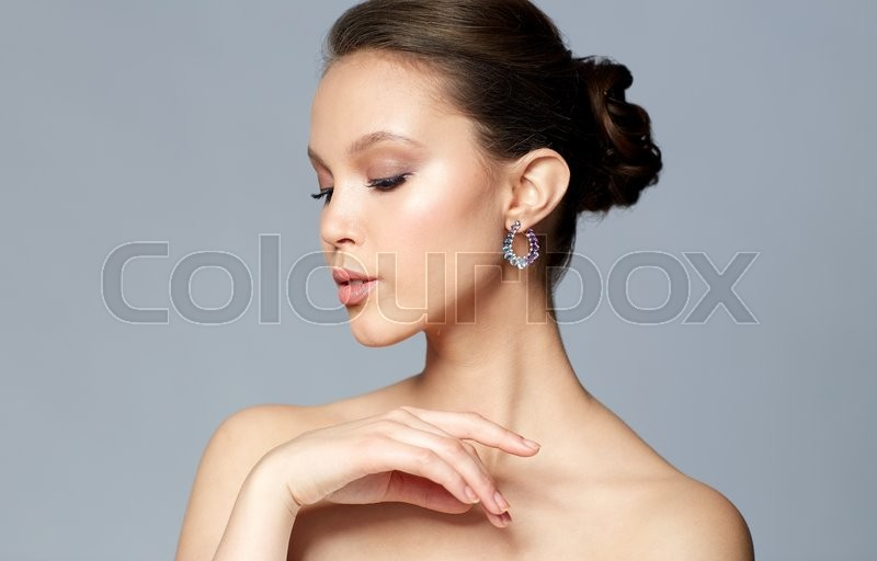 Stock image of 'beauty, jewelry, accessories, people and luxury concept - close up of beautiful asian woman face with earring over gray background'