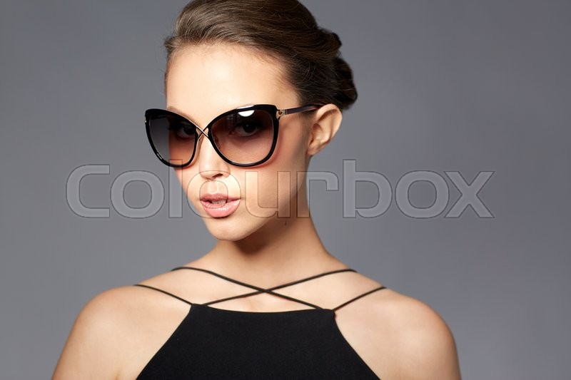 Stock image of 'accessories, eyewear, fashion, people and luxury concept - beautiful young woman in elegant black sunglasses over gray background'