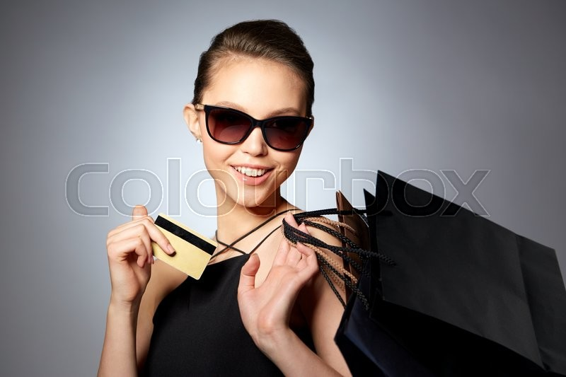 Stock image of 'sale, finances, fashion, people and luxury concept - happy beautiful young woman in black sunglasses with credit card and shopping bags over gray background'