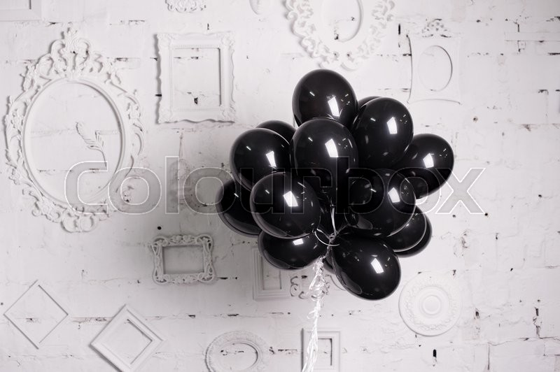 Stock image of 'black balloons against a white wall with frames.'
