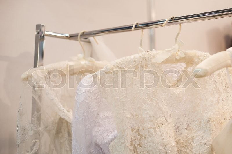 Stock image of 'Beautiful white cream wedding dresses made of silk chiffon, tulle and lace hanging on hangers with bows'