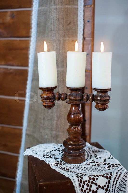 Stock image of 'Retro wooden candlestick with candles on wooden table.'