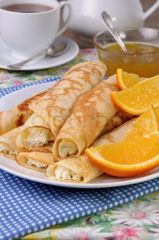 Stock image of 'Pancakes stuffed with cottage cheese and oranges for breakfast'