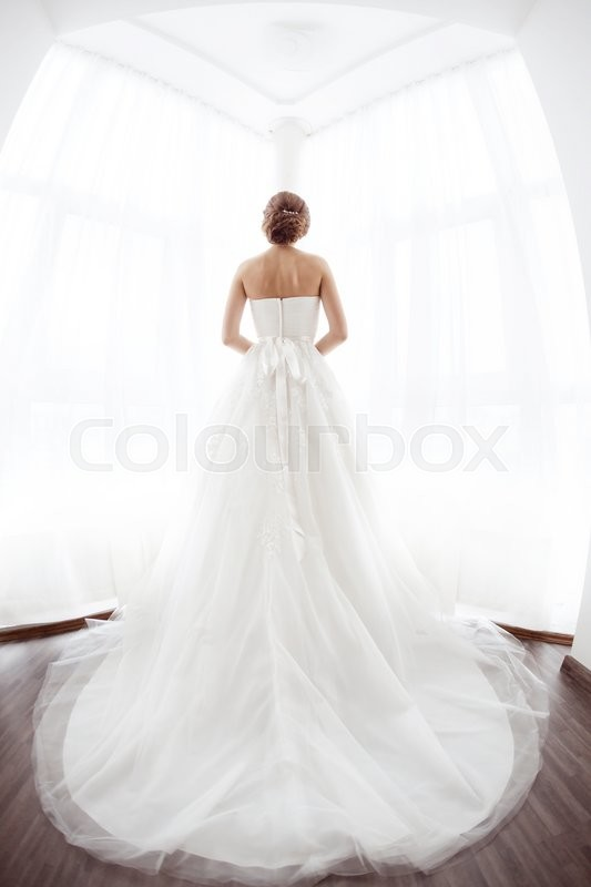 Stock image of 'Beautiful young bride in white wedding dress indoors.  Luxuty model standing against big window at home. Girl waiting her groom in bright room. High key, made on fisheye lens photo.'