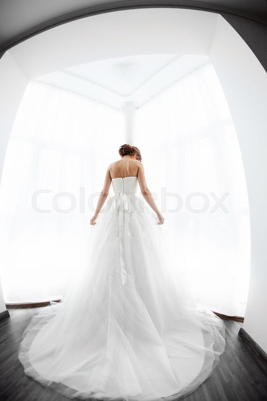 Stock image of 'Beautiful young bride in white wedding dress indoors.  Luxuty model standing against big window at home. Girl waiting her groom and prepearing her gorgeous look in bright room. High key, made on fisheye lens photo.'