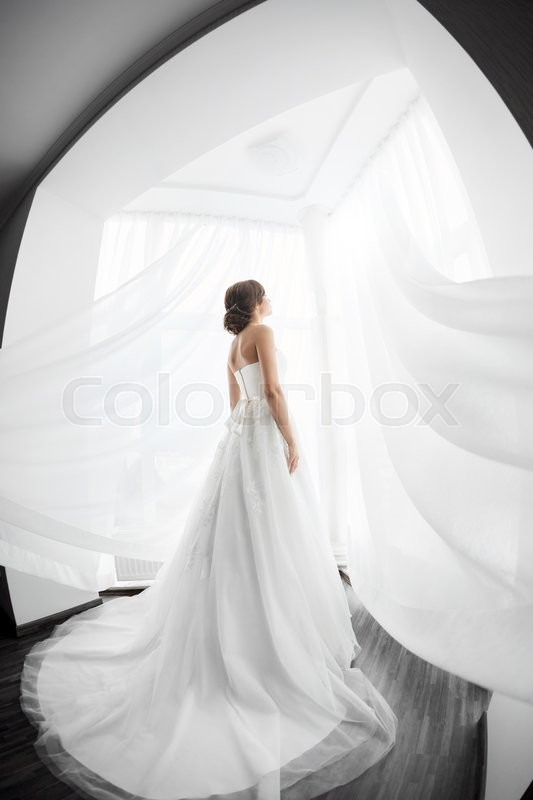 Stock image of 'Beautiful young bride in white wedding dress indoors.  Luxuty model standing in full length against big window at home. Girl waiting her groom in bright room. High key, made on fisheye lens photo.'