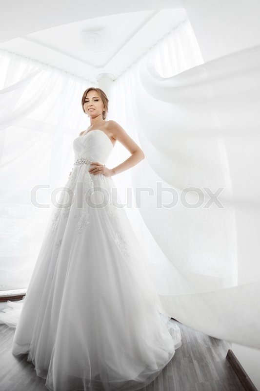 Stock image of 'Beautiful young bride in white wedding dress indoors.  Luxuty model standing in full length against big window at home. Girl waiting her groom and looking at camera in bright room. High key, made on fisheye lens photo.'
