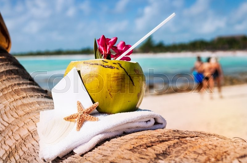 Stock image of 'Coconut cocktail starfish tropical Caribbean beach refreshment and towel'