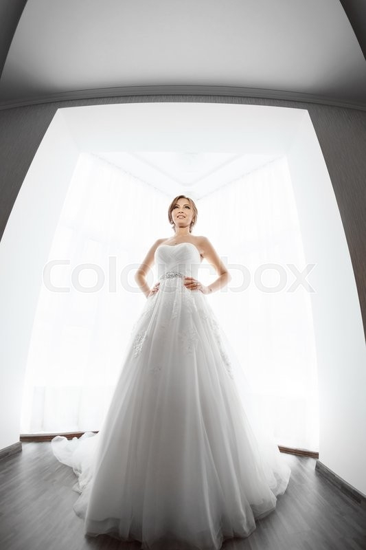 Stock image of 'Beautiful young bride in white wedding dress indoors.  Luxuty model standing in full length against big window at home. Girl looking at her groom in bright room. High key, made on fisheye lens photo.'
