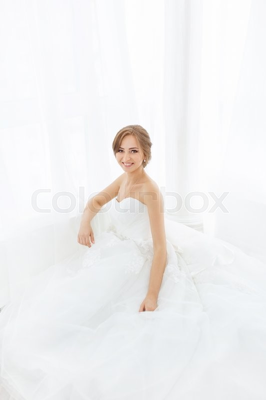 Stock image of 'Beautiful young bride smiling in white wedding dress indoors.  Luxuty model sitting against big window at home. Girl waiting her groom and looking at camera in bright room. High key photo.'