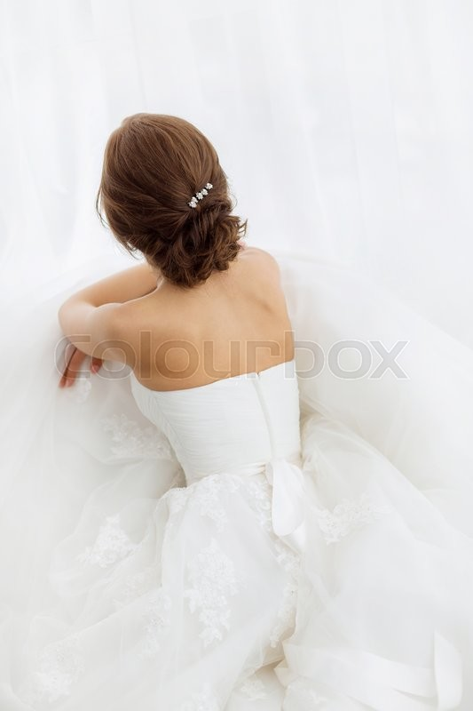 Stock image of 'Beautiful young brides back in white wedding dress indoors.  Luxuty model sitting against big window at home. Girl waiting her groom in bright room. Beautiful wedding hairdress. High key photo.'