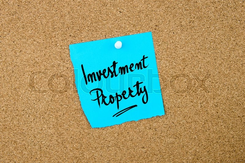 Stock image of 'Investment Property written on blue paper note pinned on cork board with white thumbtacks, copy space available'