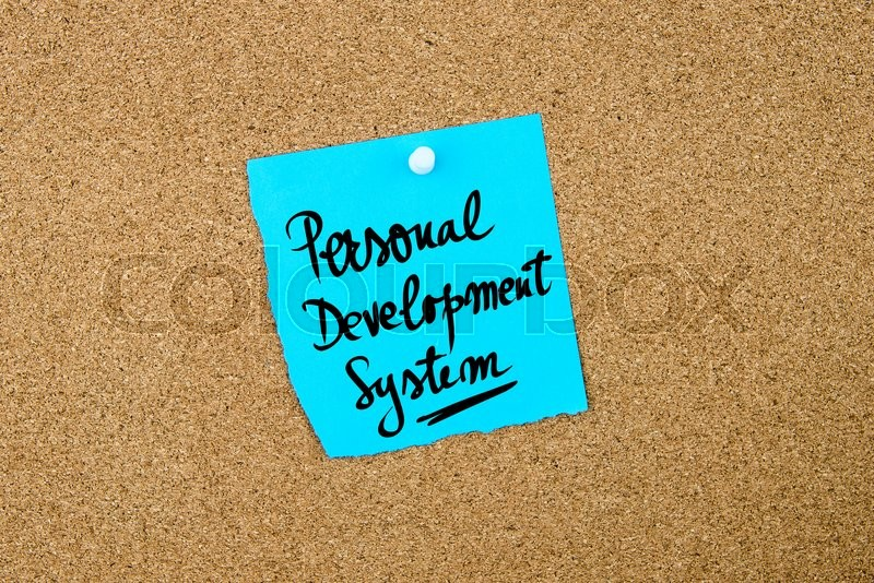 Stock image of 'Personal Development System written on blue paper note pinned on cork board with white thumbtacks, copy space available'