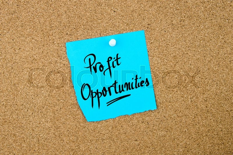 Stock image of 'Profit Opportunities written on blue paper note pinned on cork board with white thumbtacks, copy space available'