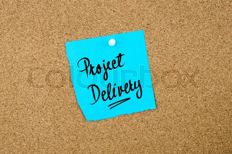 Stock image of 'Project Delivery written on blue paper note pinned on cork board with white thumbtacks, copy space available'