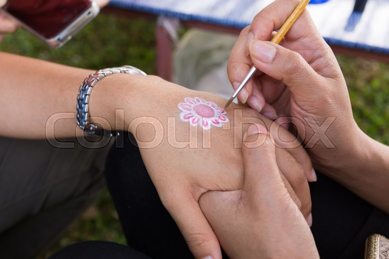 Stock image of 'Body paint, artist used paintbrush drawing art on hand person'
