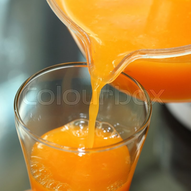 Stock image of 'Fresh orange juice pouring from a jug into the glass'