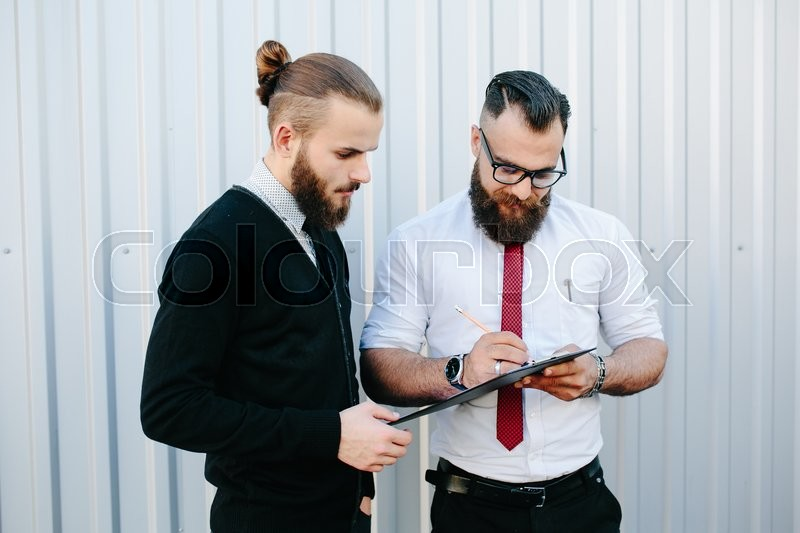 Stock image of 'Two bearded businessman signing documents in the street'