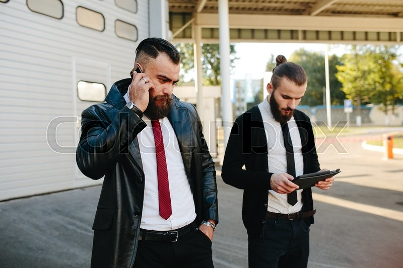 Stock image of 'Two bearded businessman working on the street'