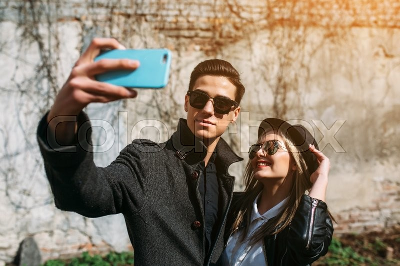 Stock image of 'Photo of a young beautiful couple making selfie on wall background'