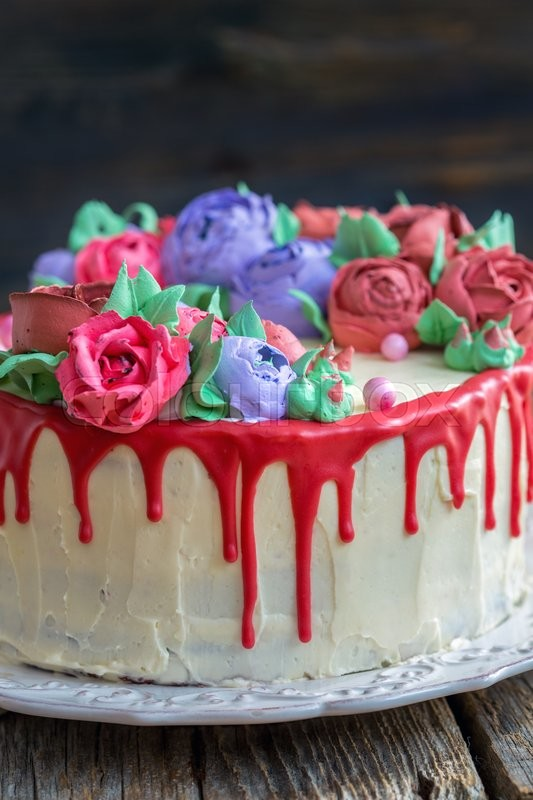 Stock image of 'Cake with colorful flowers and red with chocolate on an old table.'
