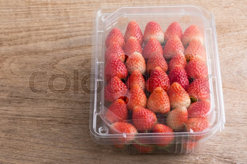 Stock image of 'Red ripe strawberry in plastic box of packaging on wood table'