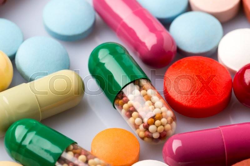 Stock image of 'Scattered colorful medical pills and pharmaceuticals remedy'