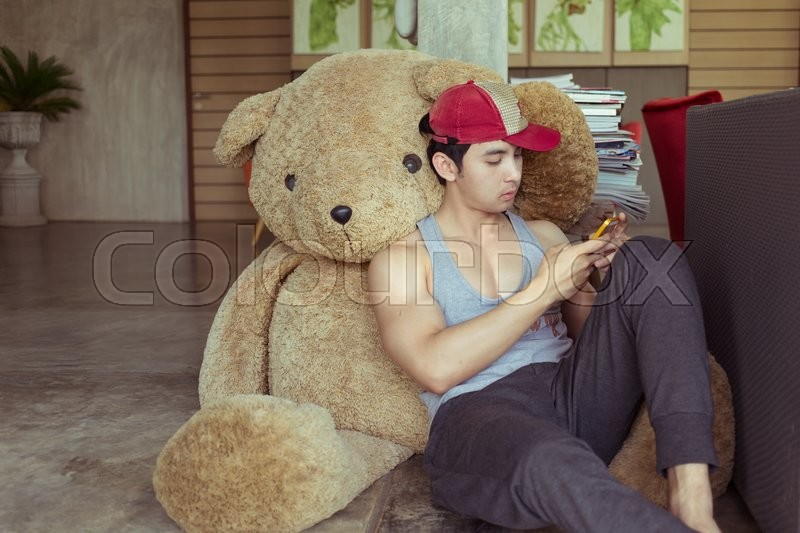 Stock image of 'Lifestyle of man using a mobile phone in home with big fluffy doll bear'