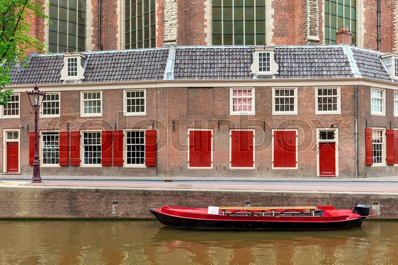 Stock image of 'Red boat on canal and typical brick dutch house on background in Amsterdam, Netherlands.'