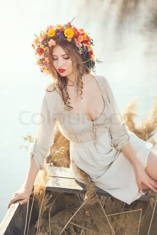 Stock image of 'Young sexy woman on boat at sunset. The girl has a flower wreath on her head, relaxing on river. Beautiful body. Fantasy art photography'