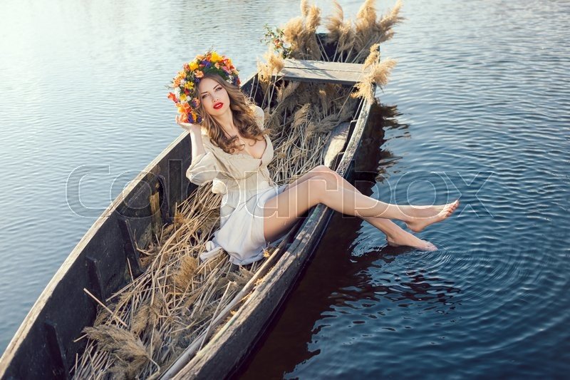 Stock image of 'Young sexy woman on boat at sunset. The girl has a flower wreath on her head, relaxing and sailing on river. Beautiful body and face. Fantasy art photography. Concept of female beauty, rest in the nature, and water travel'
