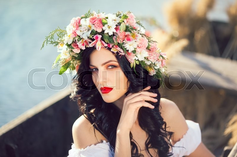 Stock image of 'Portrait of young fashion woman on boat at sunset. The girl has colorfull makeup a flower wreath on her head, posing and looking at camera. Fantasy art photography. Concept of female beauty, rest in the nature, and travel by water'