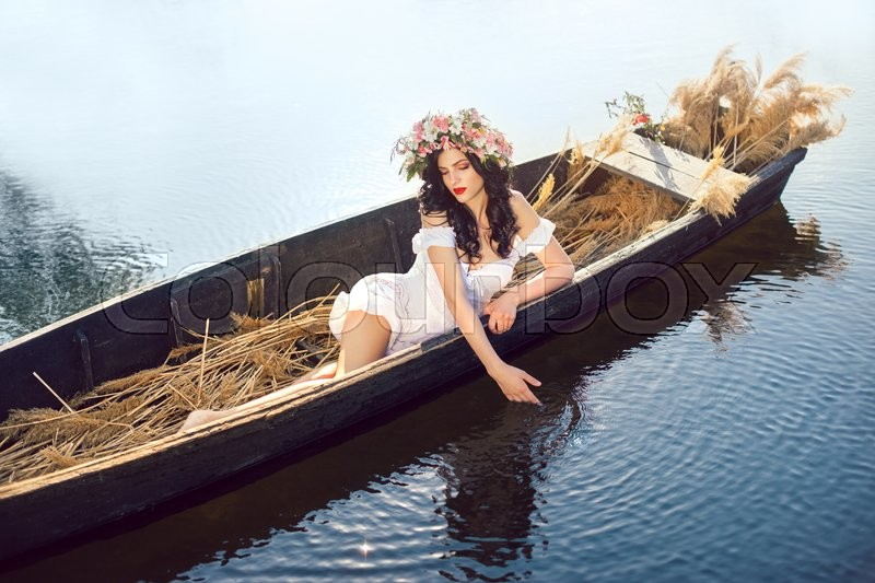 Stock image of 'Young sexy woman on boat at sunset. The girl has a flower wreath on her head, relaxing and seiling on river. Fantasy art photography. Concept of female beauty, rest in the nature, and travel by water'