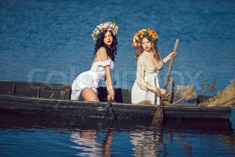 Stock image of 'Two young women on boat at sunset. Beautiful sexy slim body and cute face. Fashion art photography. Concept of female beauty, rest on the nature, and water trip'