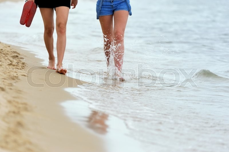 Stock image of 'Beach travel woman walking on a sand beach'