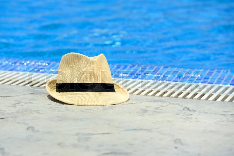 Stock image of 'Yellow sun hat on the edge of the pool'