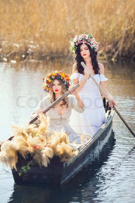 Stock image of 'Two young women on boat at sunset. The girls has a colorfull make-up and flower wreath on they head, relaxing and sailing on the river. Beautiful sexy slim body and cute face. Fashion art photography. Concept of female beauty, rest on the nature, and water trip'